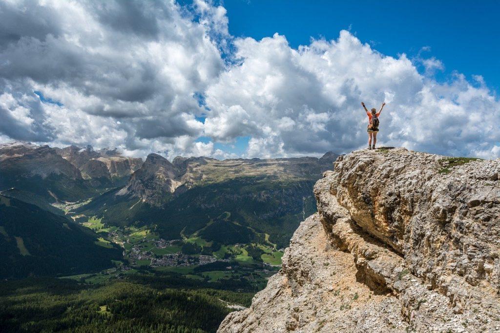Femme en haut d'une falaise heureuse